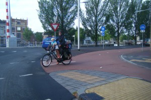 The Dutch have accomodated bicycling so well that a woman feels comfortable toting her three kids to school.