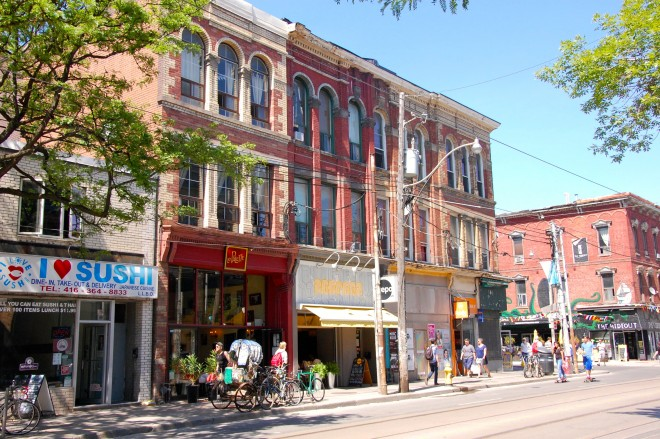 What if city planners worked in Neighborhood Planning Offices on streets like this? Queen Street West, a popular shopping street in Toronto, ON. Photo by Eric Sehr.