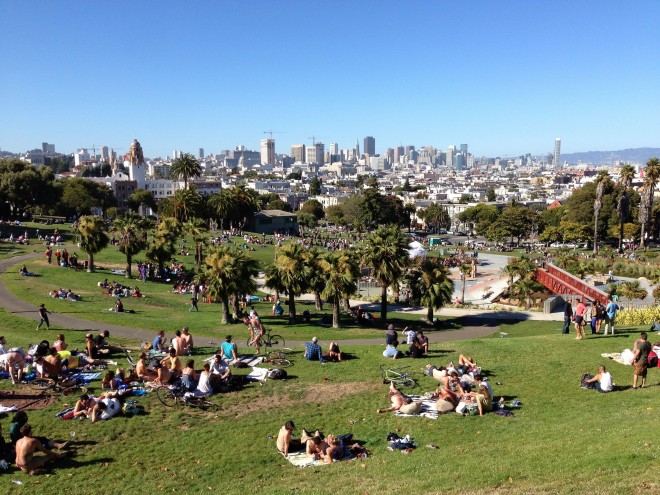 Locals relax and take advantage of the sun and spectacular views in San Francisco's Mission Dolores Park - Image by Tim Riley